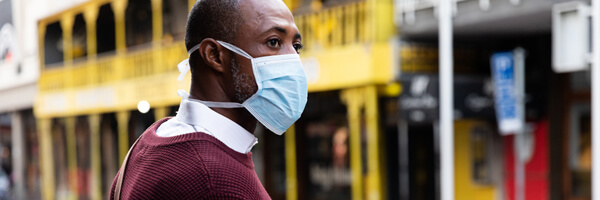 African American man out and about in the city streets during the day, wearing a face mask against air pollution and covid19 coronavirus, crossing the street and using his smartwatch.